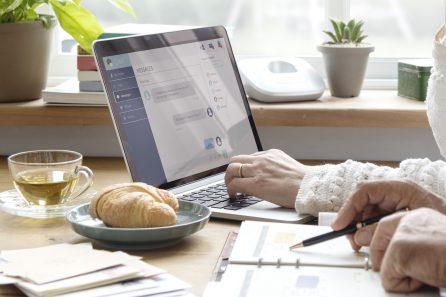 Foto: zwei Paar Hände, eine Person schreibt im Kalender, die andere tippt im Computer